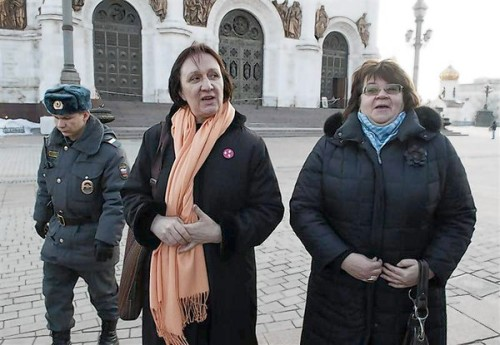 Police escort university professors Yelena Volkova and Irina Karatsuba after detaining them inside the Christ the Saviour Cathedral in Moscow
